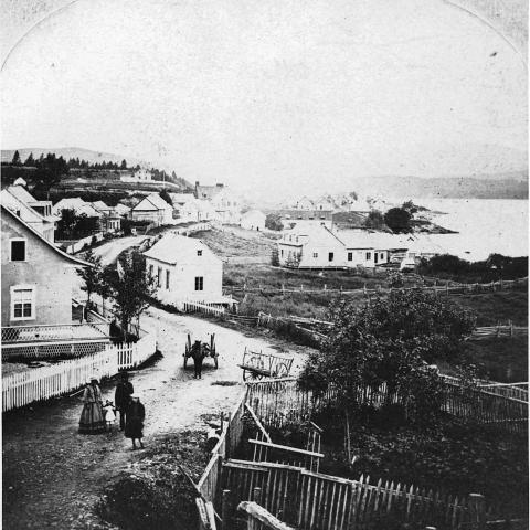 An old photograph of a hilly seaside village. A few people are in the street, near a harnessed horse.