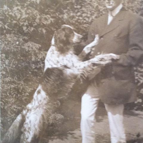 Un chien se tient sur ses pattes arrière, les pattes avant posées sur un homme habillé proprement.