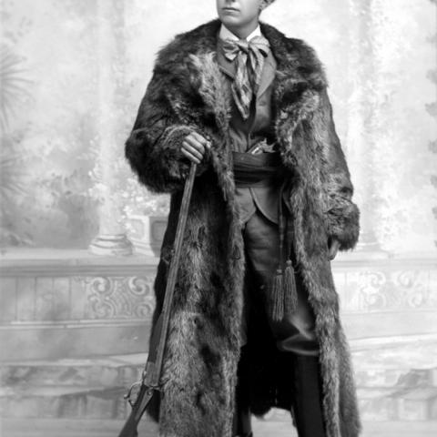 A young man wearing a fur coat and hat, and holding a hunting rifle in his hand.