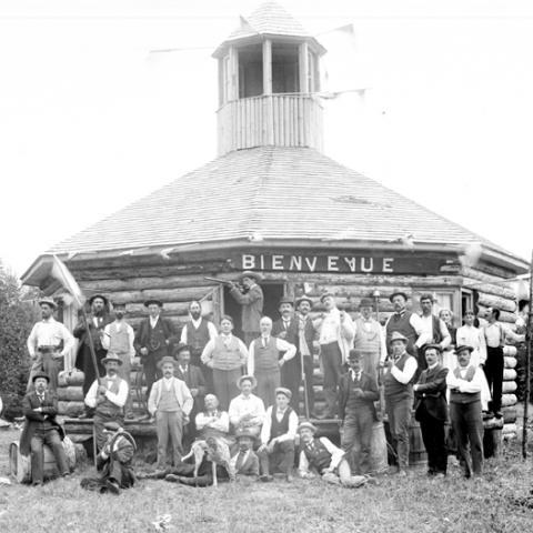 Des hommes, fusils de chasse à la main, se tiennent devant une cabane de bois rond.