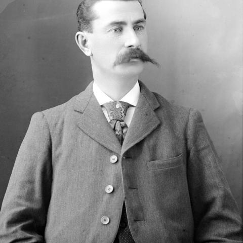 Portrait of a distinguished man sporting a prominent mustache.