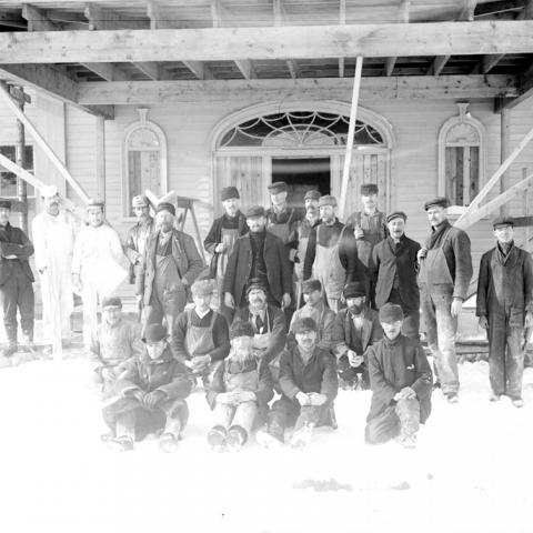 Des ouvriers posent devant une maison en construction.