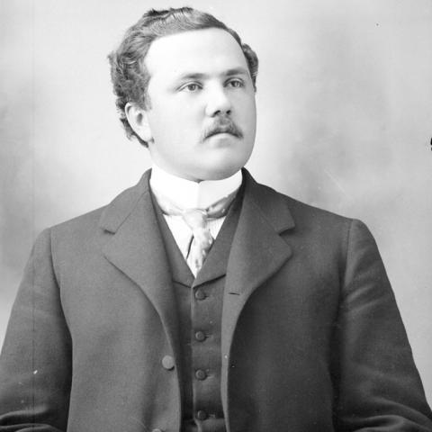 Portrait of a man sporting a mustache, coat and tie.