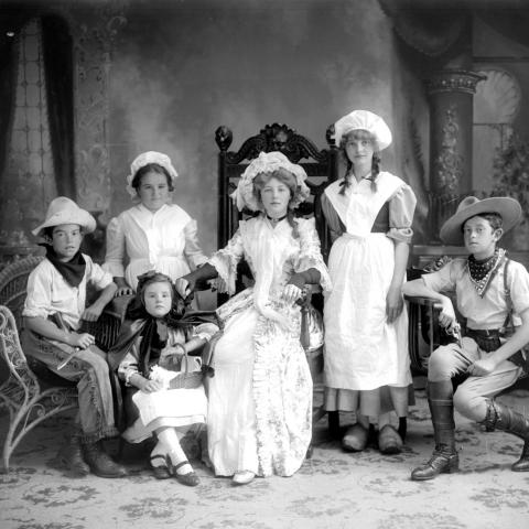 Six children in costumes posing proudly in a photographer's studio.