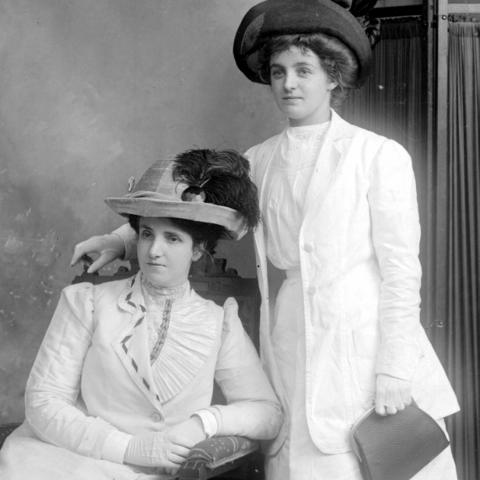 Black and white photograph of two elegant women wearing all white or very pale dresses, including gloves.