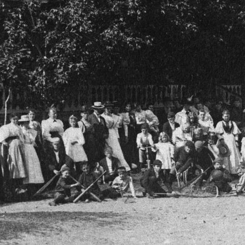 Group photograph in front of a large porch, with children showing off many pieces of sports equipment.