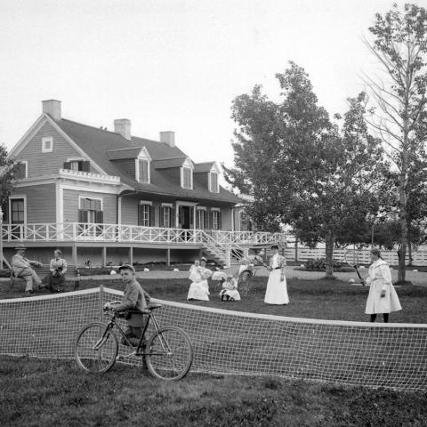 A family enjoying summer in front of a posh house and a child riding a bicycle, while others play tennis or talk.