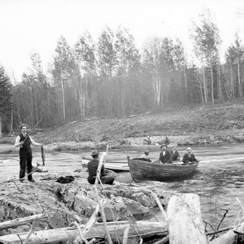Des hommes pêchent sur une rivière : certains sont en chaloupe, d'autres sur la rive.