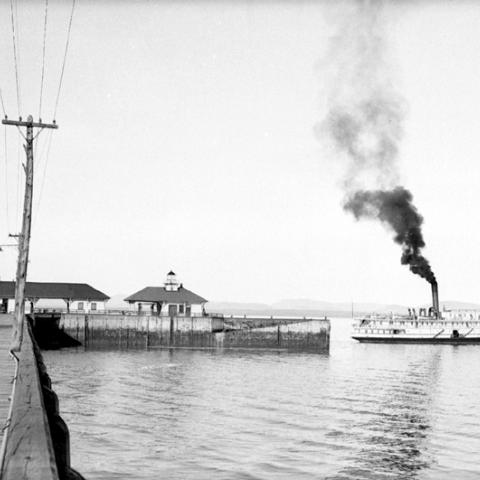 A steamboat at the end of a wharf.