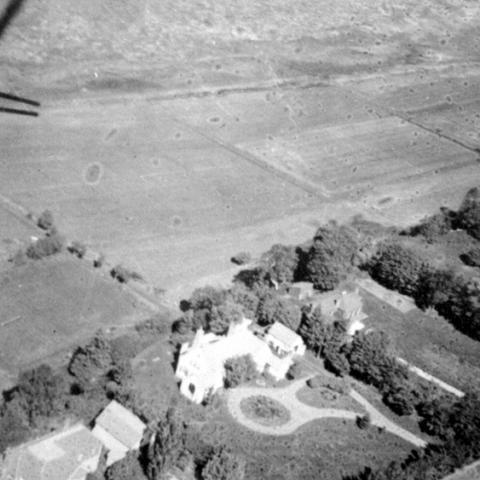 An aerial photograph in which we see a wooded estate near large fields.
