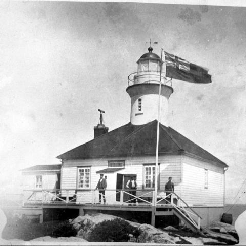 Trois hommes posent devant un phare érigé sur des rochers. Les contours de l'image forment une urne munie de deux poignées.