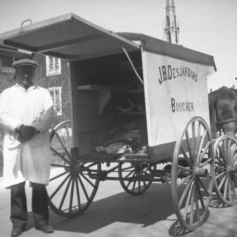 A butcher in a white smock poses in front of his horse-drawn four-wheeled delivery cart.