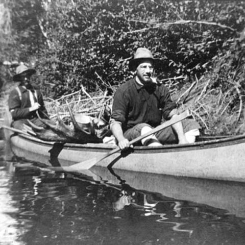 Two men in a canoe, carrying a moose.