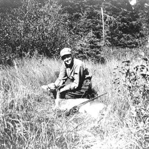 Une femme accroupie dans l'herbe présente sa prise de chasse (chevreuil).