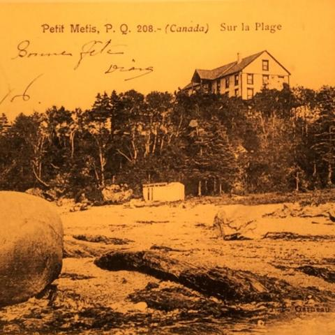 Un hôtel domine une falaise; en contrebas se trouve une plage parsemée de rochers et de cailloux.