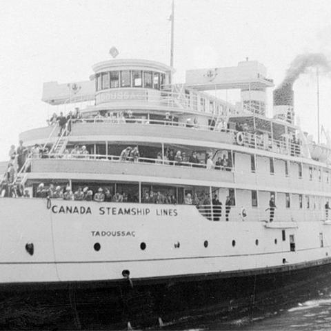 A cruise steamer with passengers on deck.