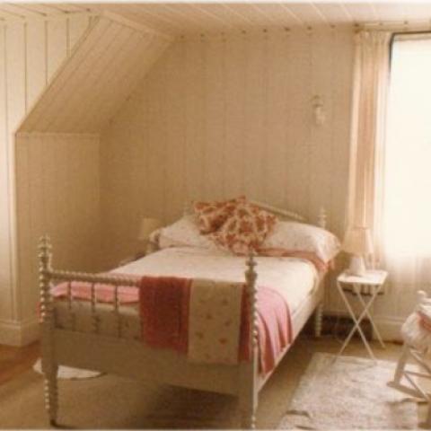 Chambre où se trouvent un lit à une place dont la base est en bois tourné, une commode, une berçante et un petit bureau.
