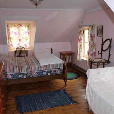A colour photograph of a small bedroom with old-fashioned furnishings
