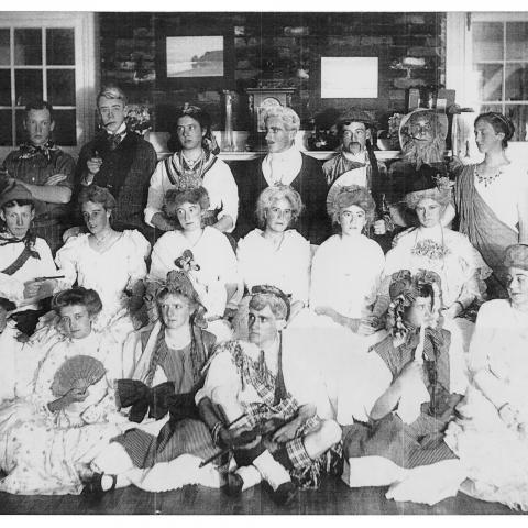 Une vingtaine d'adolescents déguisés pour une fête prennent la pose à l'intérieur d'une villa.