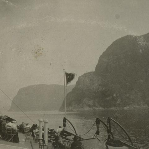 Passengers sitting on the bridge of a steamer, looking at the steep mountains on the shore.