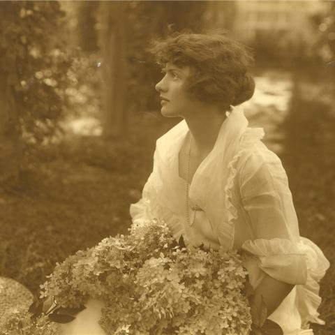 A profile of young woman holding an enormous bouquet and wearing a light-weight white blouse.