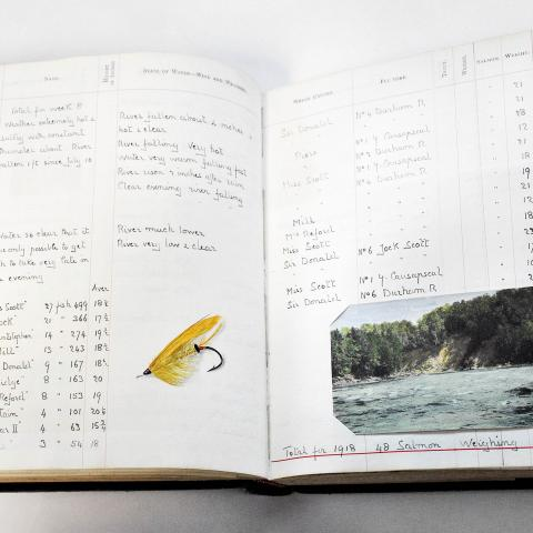 A handwritten notebook with a fly-fishing lure glued in and a colour illustration.