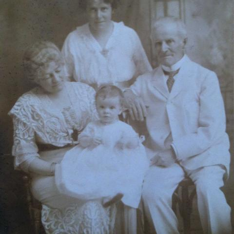 Black and white portrait of the family, sitting.