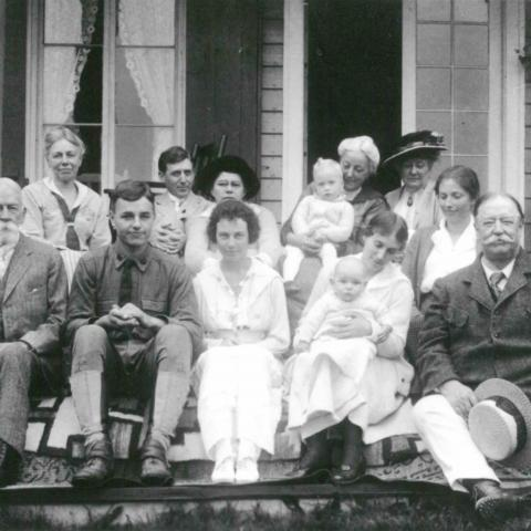 A dozen people of all ages posing for a family photograph on the steps of a summer home.