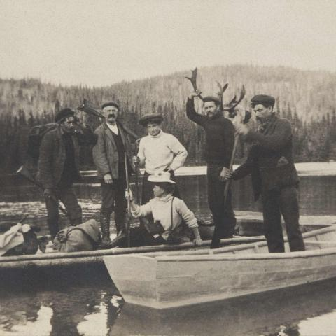 A small group of men and women in canoes, near a wharf.