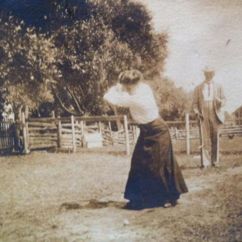 A woman swinging to hit a golf ball while a man waits in the background.