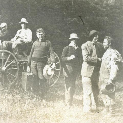 Men standing near a horse-drawn carriage meet a man in working clothes.