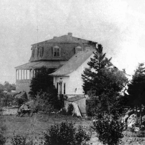 Photographie ancienne d'une maison de campagne entourée d'arbres, avec une falaise en arrière-plan.