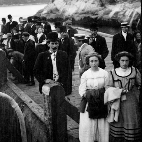 People standing on a wharf against a backdrop of mountains
