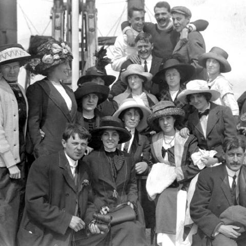 Un groupe d'hommes et de femmes; celles-ci portent des chapeaux à la décoration chargée.