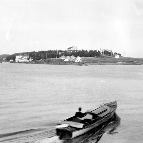 A man in a small boat heading towards the Point.