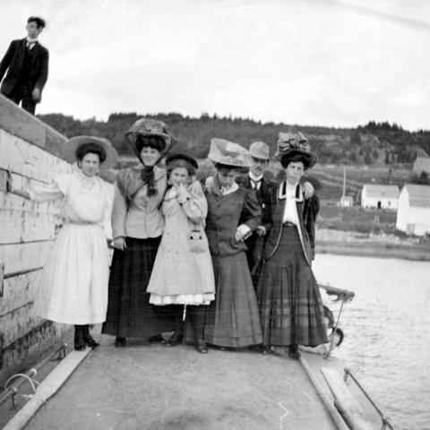 A group, mostly women wearing large hats, at the foot of a wharf.