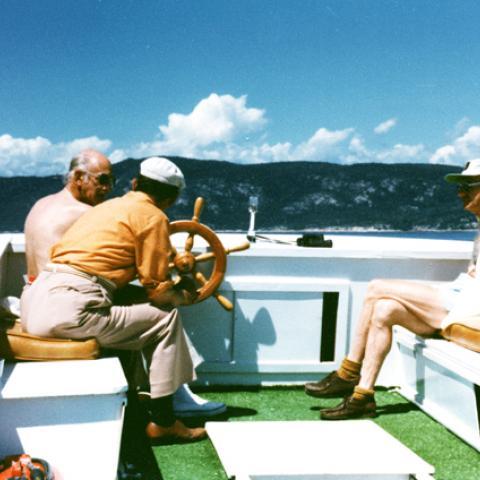 Three men on a small boat.