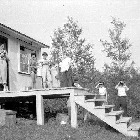 A dozen or so people behind a cottage in casual dress, two holding binoculars.