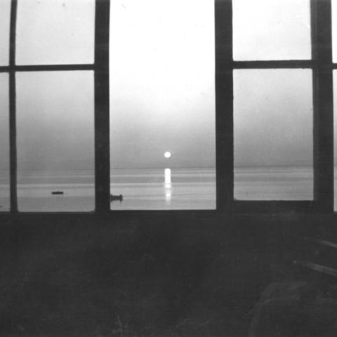 An old woman sitting at a window, watching the sun set over the St. Lawrence.