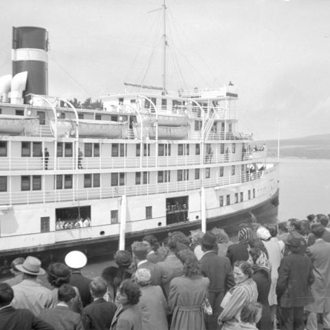 Dozens of passengers waiting on a wharf where a very large cruise steamer is moored.