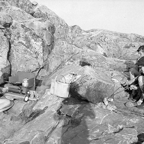 Young women cooking hotdogs on a rock.