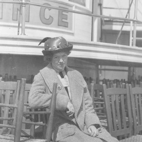 Une jeune femme est assise sur le pont d'un navire, entourée de chaises empilées.