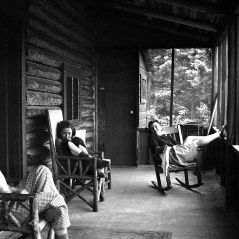 Three young women rocking on the porch of a log cabin.