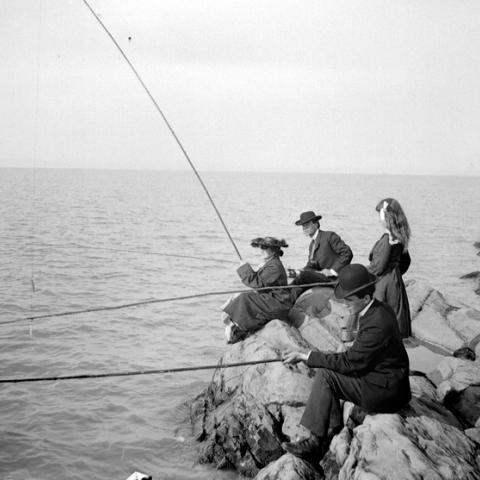 Deux hommes et deux femmes pêchent le poisson, assis sur des rochers.