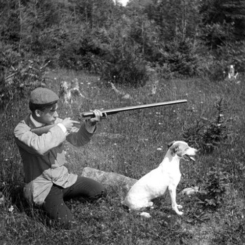 A young man is kneeling in the grass with his dog, hunting rifle in hand.