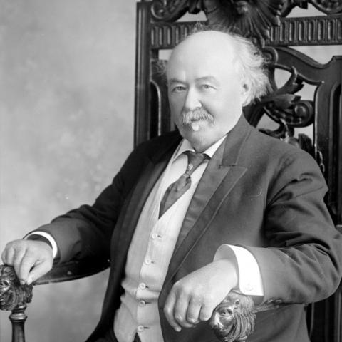 Portrait d'un homme assis dans une chaise dont les accoudoirs sont en forme de tête de lion.