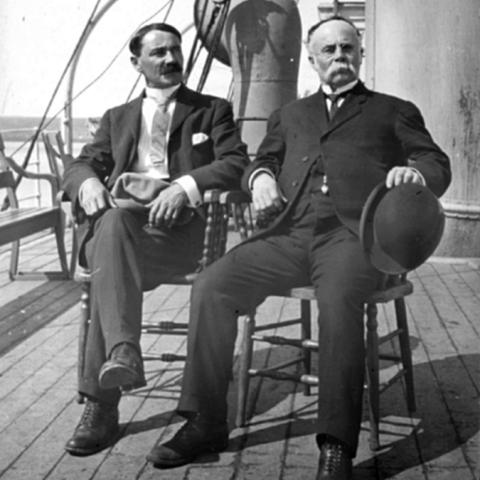 Two men sitting on chairs on the deck of a boat.