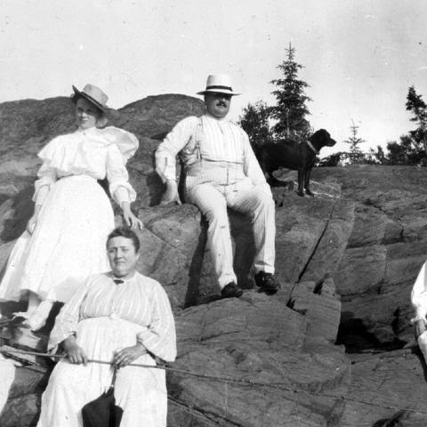 Five adults wearing white and sitting on a rock, with two dogs. One of the women is holding a fishing rod.