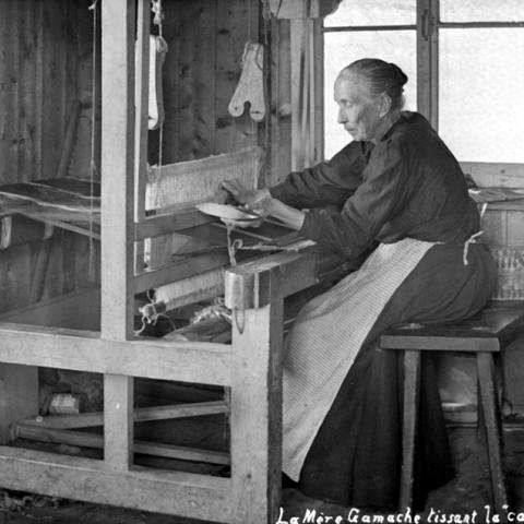 Une vieille femme travaille à son métier à tisser.
