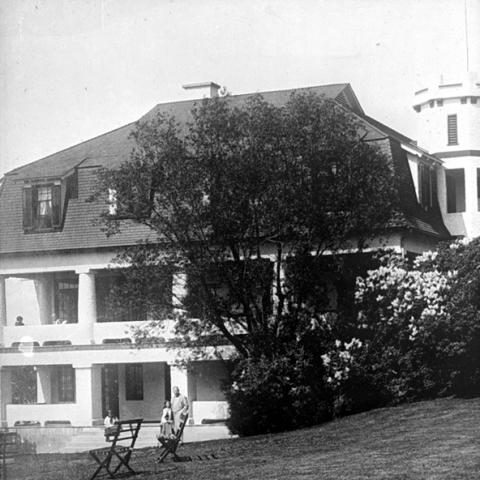 A large house with broad porches on two floors all around and a turret.